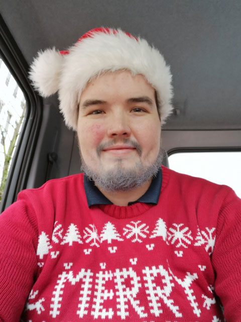 Chris Whitten in a Santa Hat and Christmas sweater